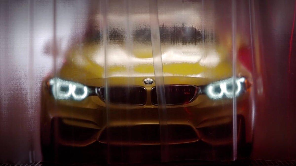 BMW M4 driftet auf Rennstrecke über den Dächern einer Fabrik