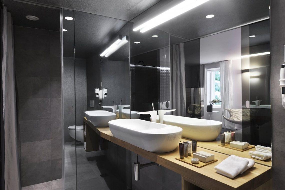 Vander Urbani Resort Ljubljana Designhotel Badezimmer Waschbecken Toilette Dusche Vanity Kit Shampoo Bodylotion Spülung Handtücher Fliesen