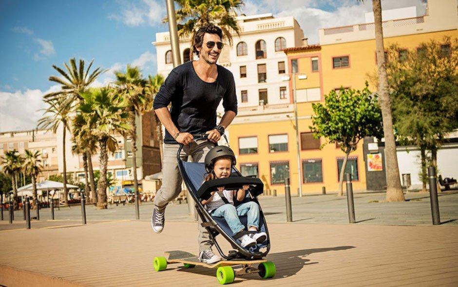 Quinny Longboard Stroller Kinderwagen Skateboard Vater Sohn Mittelmeer Spanien Barcelona Anschieben Sport Fun Elternsein Gadget innovativ sportlich Spaß