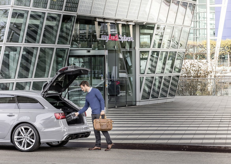 Audi on demand Mietwagen Audi RS6 grau Mann lädt Kofferund  Handgepäck in Auto