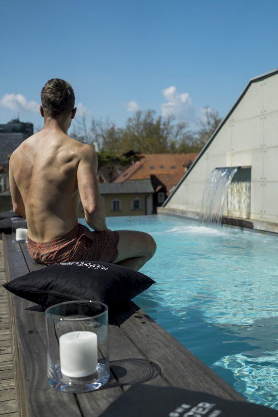 Vander Urbani Resort Ljubljana Designhotel Pool Dachterrasse Rooftop Rücken Badehose Kerze Kissen