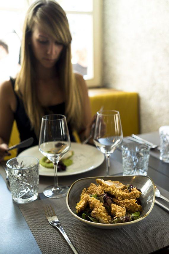 Vander Urbani Resort Ljubljana Designhotel Restaurant Lunch Menu Chicken Fingers Salad Salat Dorade Drout Fish Diana Weingläser Gelbe Sitzbank Fenster Blond Frau Besteck Schüssel