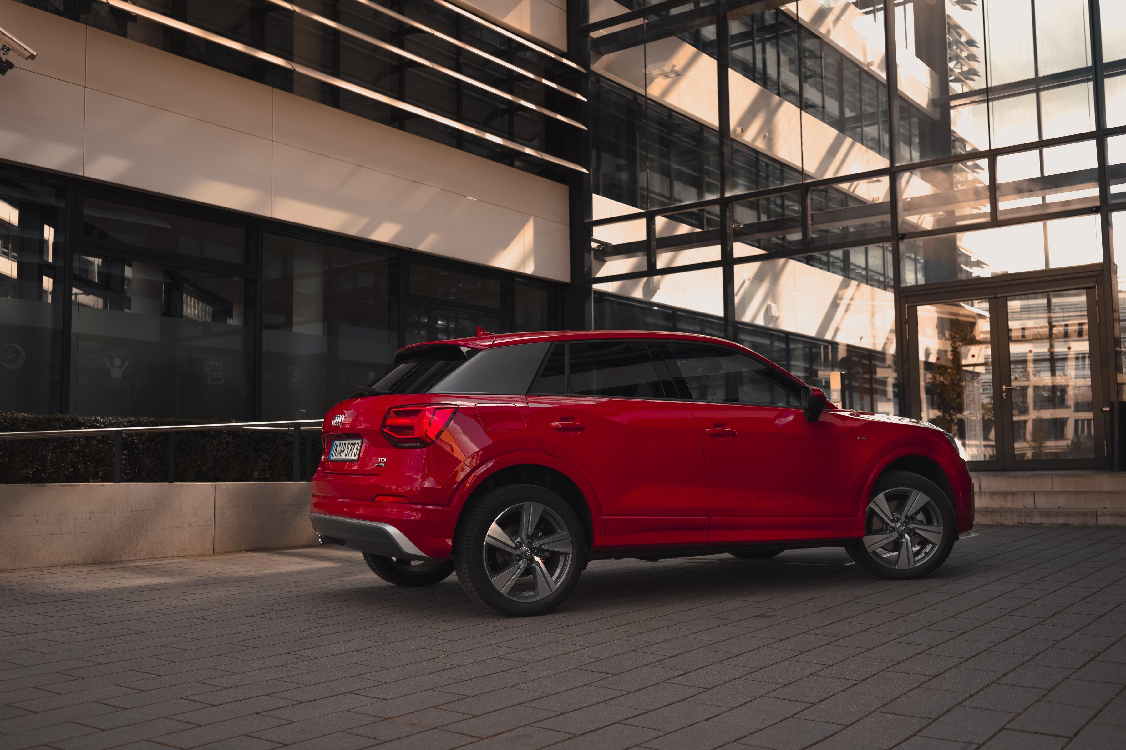 Audi Q2 Customizing Sport Sline rot Sonnenuntergang moderne Gebäudefront