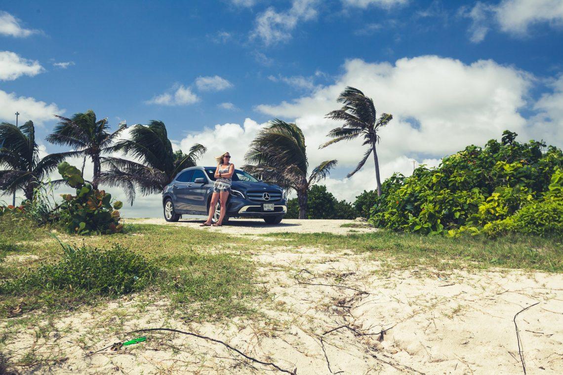 Frau vor Mercedes-Benz GLA am Strand vor Palmen