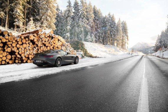 Mercedes-AMG GTS Baumstämme Holzstapel Schnee Nasse Strasse