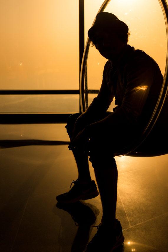 Schwebesessel Silhouette Mann mit Hut Gegenlicht Sonnenuntergang Fenster