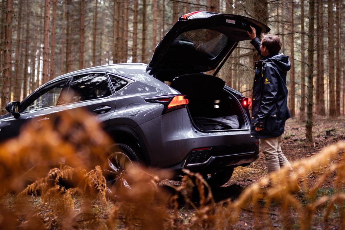 Mann am Kofferraum von Lexus NX in der Natur