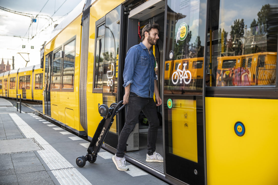 Zusammengeklappter Audi e-tron Scooter wird von einem Mann in die Straßenbahn gezogen