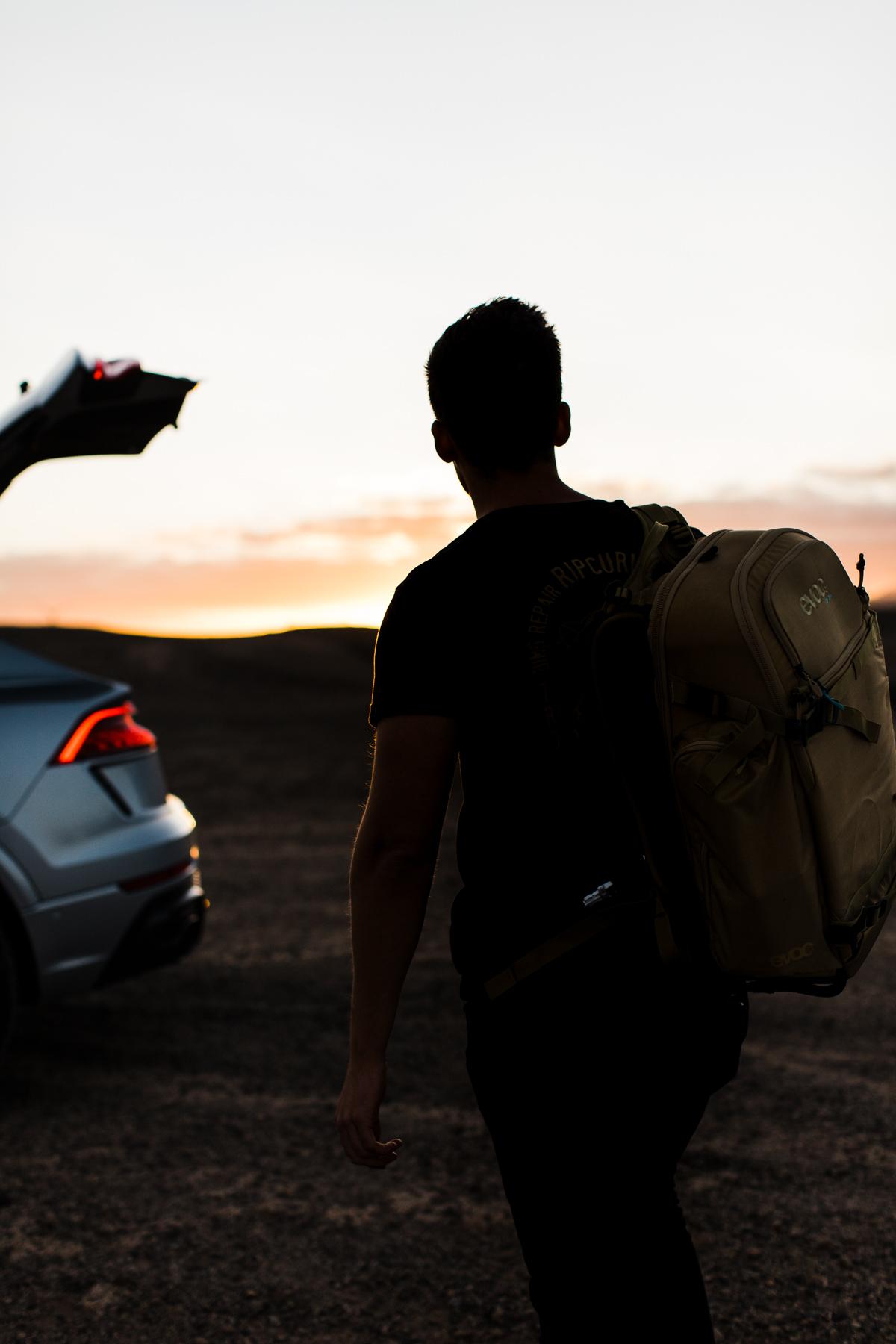 mann rucksack auto sonnenuntergang